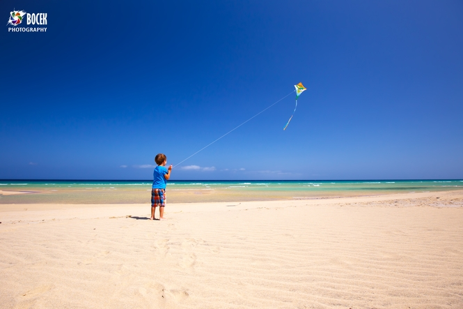 Happy little boy playing with kite on the beach, Fuerteventura,