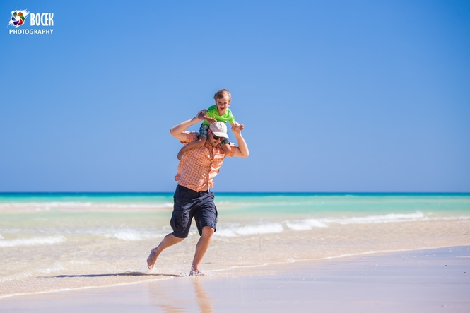 Father and his little son having fun and running on the beach.